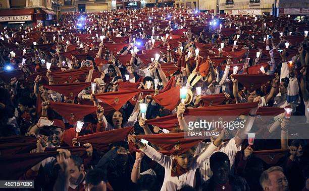 Revellers raise red scarves and candles as they sing the song 'Pobre de Mi' marking the end of the San Fermin festival in Pamplona early on July 15...