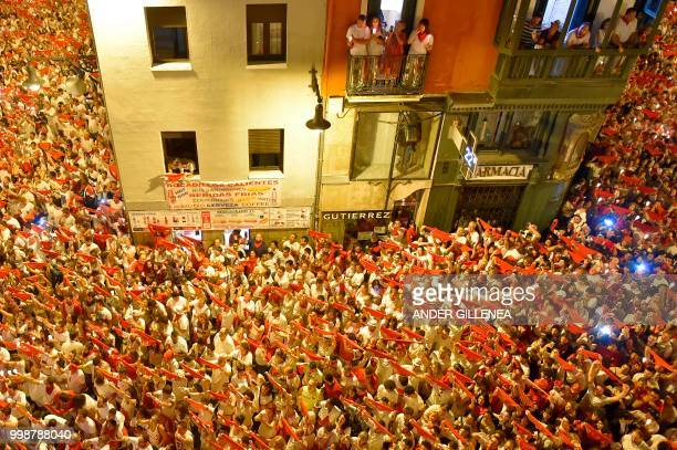 Revellers raise red scarves and candles as they sing the song 'Pobre de Mi' marking the end of the San Fermin festival in Pamplona northern Spain on...
