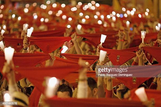 Revellers raise their scarves and candles as they sing the 'Pobre de Mi' song marking the end of the San Fermin festival on July 15 2014 in Pamplona...