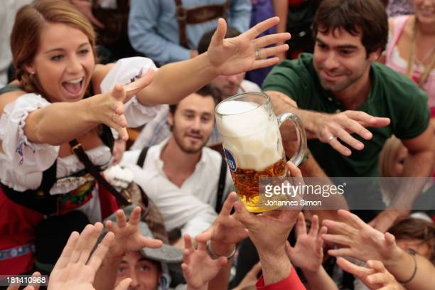 Revellers reach for the first beer mug at Hofbraeuhaus beer tent during day 1 of the Oktoberfest 2013 beer festival at Theresienwiese on September 21...