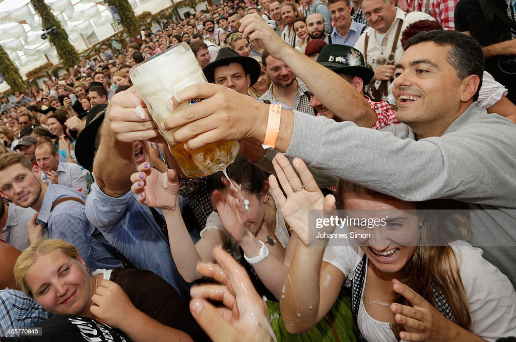Revellers reach for the first beer mugs at Hofbraeuhaus beer tent during the opening day of the 2014 Oktoberfest on September 20, 2014 in Munich, Germany. The 181st Oktoberfest will be open to the public from September 20 through October 5 and traditionally draws millions of visitors from across the globe to the the world's largest beer festival.