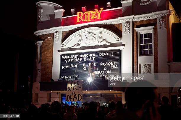 Revellers rearrange the letters on the outside of the Ritzy cinema in south London in the early hours of April 9 to read 'Margaret Thatcher Dead' as...