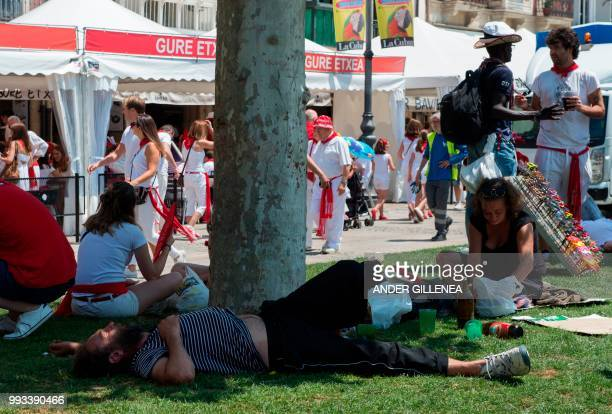 Revellers rest on the first day of the San Fermin bull run festival in Pamplona northern Spain on July 7 2018 Each day at 8am hundreds of people race...