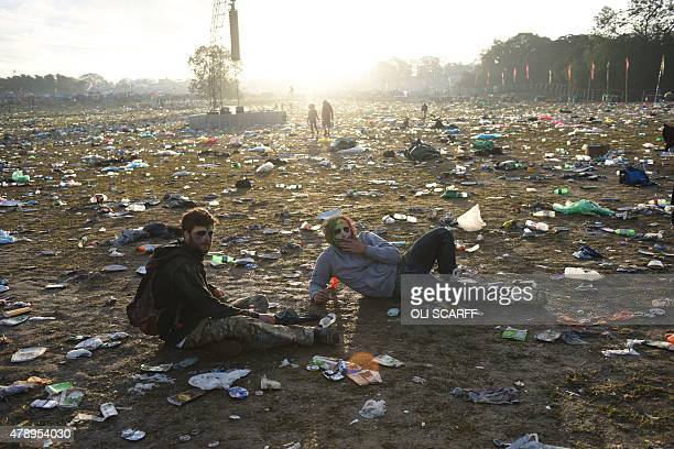 Revellers rest on the ground surrounded by discarded litter at the Glastonbury Festival of Music and Performing Arts on Worthy Farm near the village...