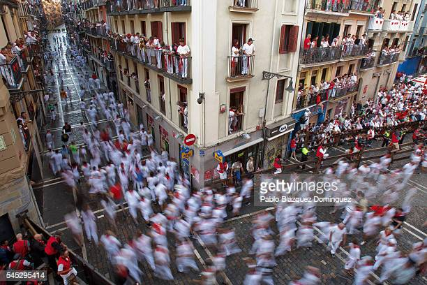 Revellers run entering Estafeta Street before the start of Fuente Ymbro's fighting bulls running during the second day of the San Fermin Running of...