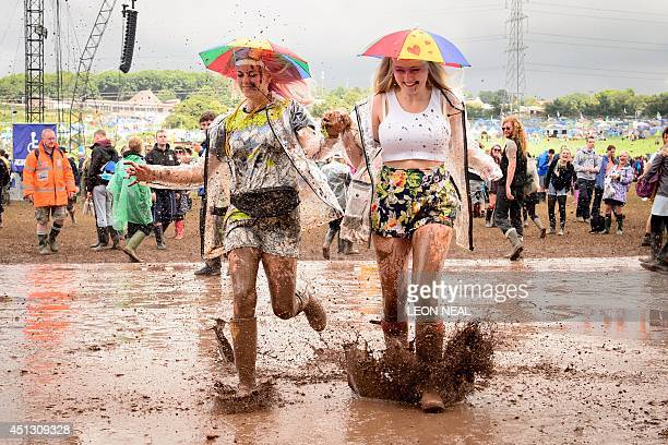 Revellers run through a puddle as they pose for photographers on the first official day of the Glastonbury Festival of Music and Performing Arts on...
