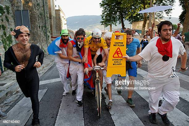 Revellers run with a cyclist depicting 'Miguel Indurain' during the Villavesa running after the San Fermin festival finished on July 15, 2015 in...
