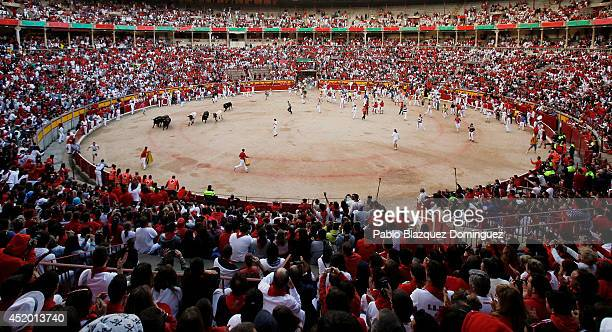 Revellers run with a Jandilla's fighting bull inside the bullring during the sixth day of the San Fermin Running Of The Bulls festival on July 11...