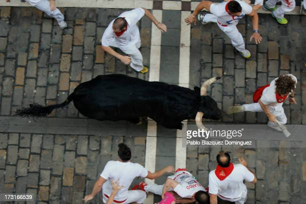 Revellers run with a Valdefresno's ranch fighting bull at Calle Estafeta during the fourth day of the San Fermin Running Of The Bulls festival on...