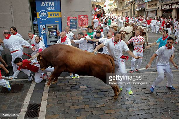 Revellers run with Cebada Gago's fighting bulls entering Estafeta Street as a bull charge over runners during the third day of the San Fermin Running...