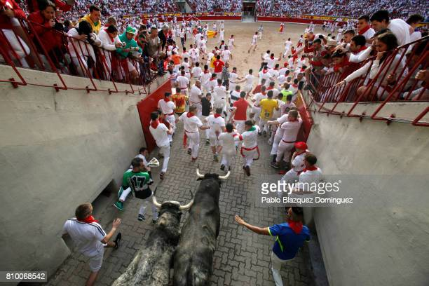 Revellers run with Cebada Gago's fighting bulls entering the bullring during the second day of the San Fermin Running of the Bulls festival on July 7...