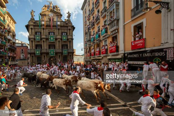Revellers run with Cebada Gagos's fighting bulls before at Plaza Consistorial during the third day of the San Fermin Running of the Bulls festival on...