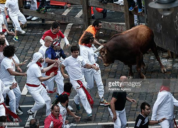 Revellers run with fighting bulls during the San Fermin Running of the Bulls festival on July 8 2016 in Pamplona Spain The San Fermin Festival is...