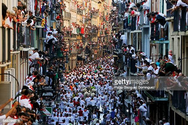 Revellers run with Fuente Ymbro's fighting bulls along Estafeta Street during the second day of the San Fermin Running of the Bulls festival on July...