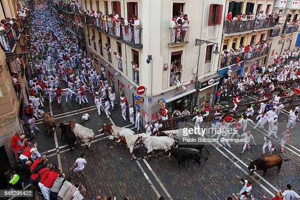 Revellers run with Fuente Ymbro's fighting bulls entering Estafeta Street during the second day of the San Fermin Running of the Bulls festival on...