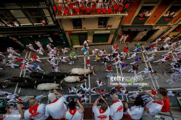 Revellers run with Jandilla's fighting bulls along Calle de Estafeta during the fifth day of the San Fermin Running of the Bulls festival on July 10,...