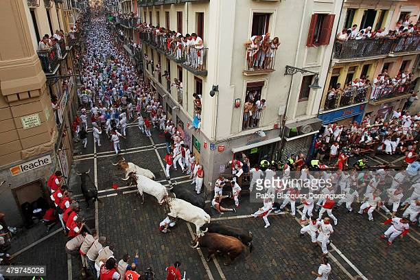 Revellers run with Jandilla's fighting bulls along the Calle Estafeta during the second day of the San Fermin Running Of The Bulls festival on July 7...