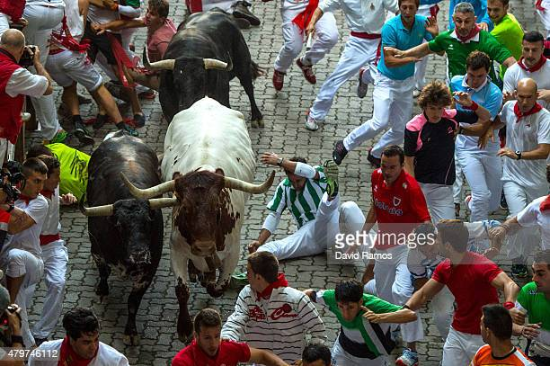 Revellers run with Jandilla's fighting bulls entering the bullring during the second day of the San Fermin Running of the Bulls festival on July 7...