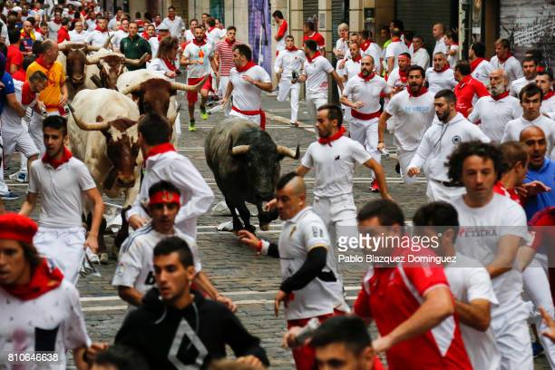 Revellers run with Jose Escolar Gil's fighting bulls at Curva Estafeta during the third day of the San Fermin Running of the Bulls festival on July 8...