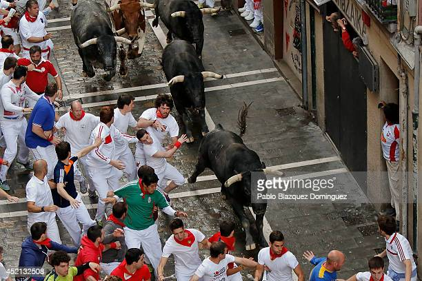 Revellers run with Miura's fighting bulls at Calle Estafeta during the ninth day of the San Fermin Running Of The Bulls festival on July 14 2014 in...