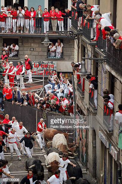 Revellers run with Miura's fighting bulls at Curva Estafeta as people look over from balconies during the ninth day of the San Fermin Running Of The...