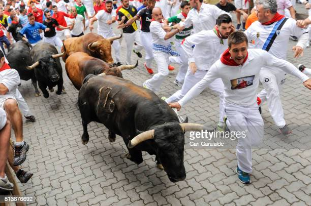 Revellers run with Nunez del Cuvillo's fighting bulls during the eighth day of the San Fermin Running of the Bulls festival on July 13, 2017 in...