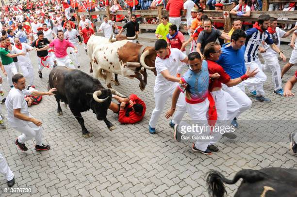 Revellers run with Nunez del Cuvillo's fighting bulls during the eighth day of the San Fermin Running of the Bulls festival on July 13 2017 in...