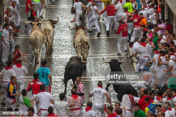 Revellers run with Puerto de San Lorenzo's fighting bulls along Calle Estafeta during the second day of the San Fermin Running of the Bulls festival...