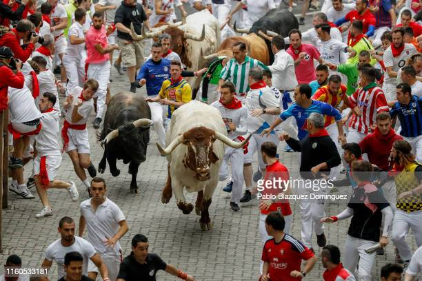 Revellers run with Puerto de San Lorenzo's fighting bulls before entering the bullring during the second day of the San Fermin Running of the Bulls...