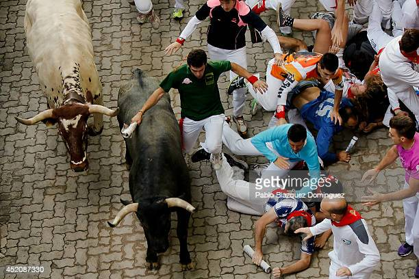 Revellers run with the Adolfo Martin Andres's fighting bulls at the end of the run during the eighth day of the San Fermin Running Of The Bulls...