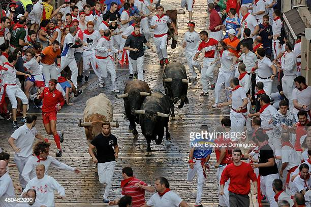 Revellers run with the Herederos del Excelentisimo Conde de la Maza's fighting bulls along Mercaderes Street during the seventh day of the San Fermin...