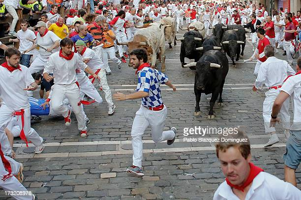 Revellers run with Vitoriano del Rio's ranch fighting bulls at Curva Estafeta during the fith day of the San Fermin Running Of The Bulls festival on...