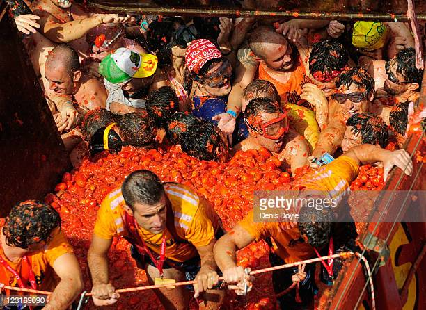 Revellers scoup tomatoes from a truck during the annual tomatina festival on August 31 2011 in Bunol Spain An estimated 35000 people threw 120 tons...