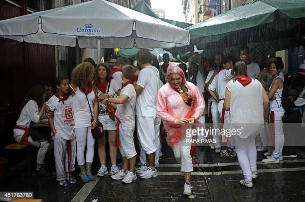 Revellers shelter from heavy rainfall on the first day of the San Fermin Festival in Pamplona northern Spain on July 6 2014 A redandwhite sea of...