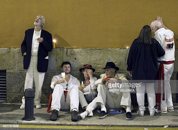Revellers sit after singing 'Pobre de Mi' which marks the end of the San Fermin festival in Pamplona early on July 15 2014 The festival is a symbol...