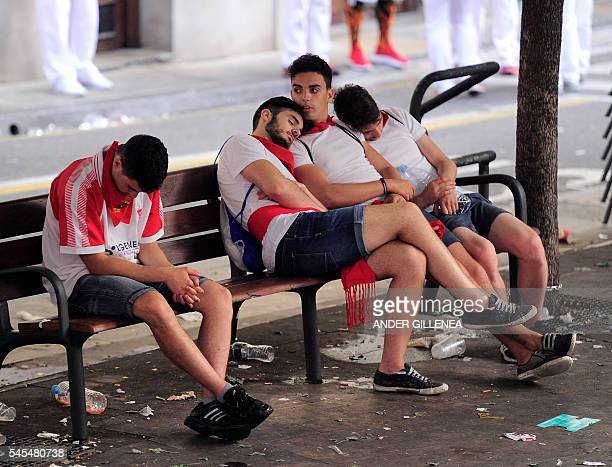 Revellers sleep on a bench in the street on the second day of the San Fermin bull run in Pamplona northern Spain on July 8 2016 On each day of the...