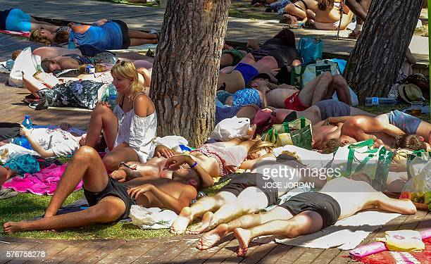 Revellers sleep or take a break on the grass near a beach on the fourth and last day of the 2016 Benicassim International Festival in Benicassim in...