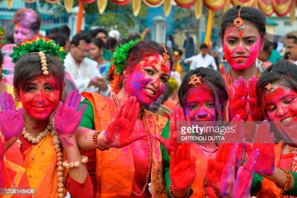 Revellers smeared in colour powder pose for a picture as they celebrate Holi the spring festival of colours in Siliguri on March 9 2020