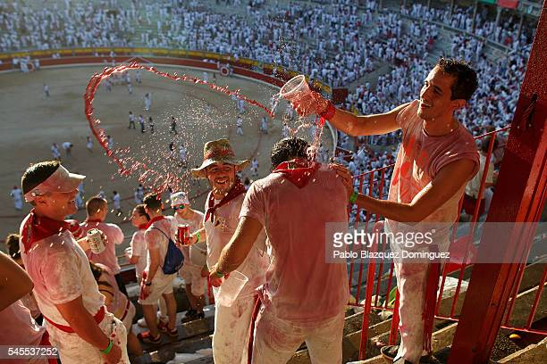 Revellers spray drinks as they enjoy the atmosphere inside Pamplona's bullring during a bullfight on the third day of the San Fermin Running of the...