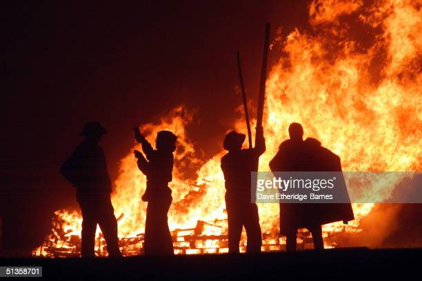 Revellers stand near the fires during the first of the Bonfire Night celebrations on September 25 2004 in Burgess Hill England Bonfire Night is...