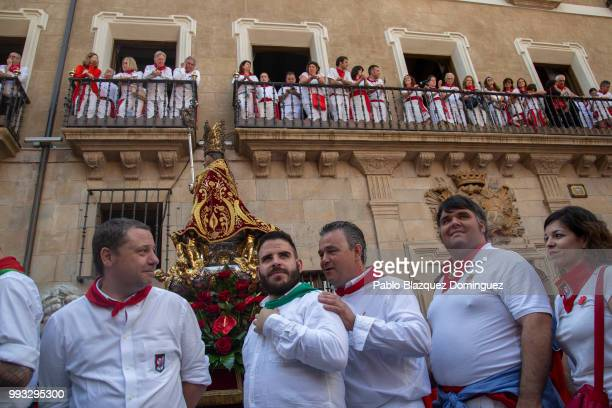 Revellers stand next to a figure of San Fermin during the San Fermin procession on the second day of the San Fermin Running of the Bulls festival on...