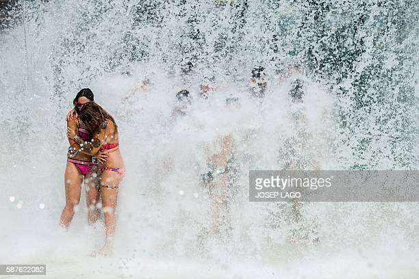 Revellers stand under a water cascade during the Circuit Festival's Water Park Day an open air gay party in Vilassar de Mar near Barcelona on August...