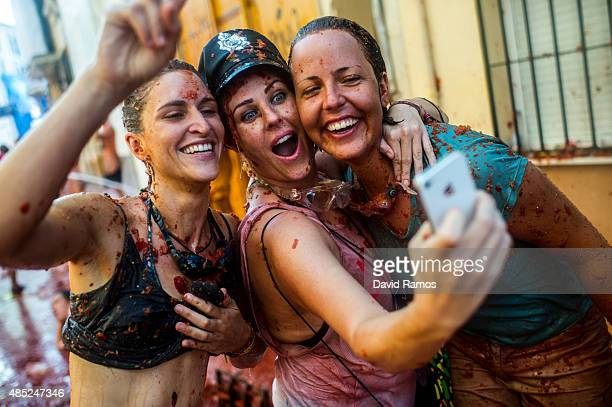 Revellers take a selfie as they enjoy the atmosphere in tomato pulp while participating the annual Tomatina festival on August 26 2015 in Bunol Spain...