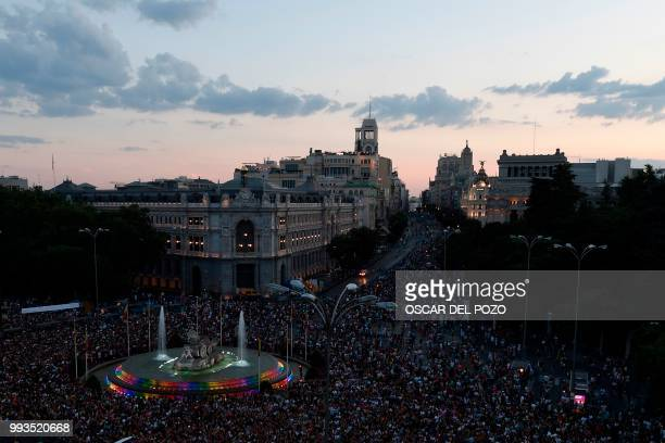Revellers take part in the Gay Pride 2018 parade at the Cibeles square illuminated with the colors of the rainbow flag in Madrid on July 7 one of the...