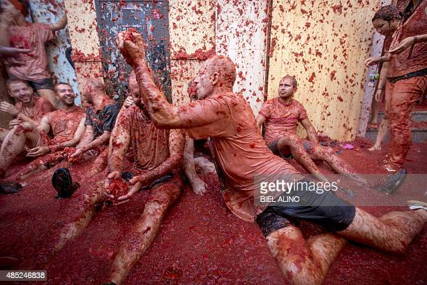 Revellers throw tomato pulp at each other during the annual 'tomatina' festivities in the village of Bunol near Valencia on August 26 2015 Some 22000...