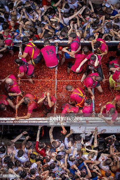 Revellers throw tomato pulp in the annual 'tomatina' festivities in the village of Bunol near Valencia on August 26 2015 Some 22000 revellers hurled...