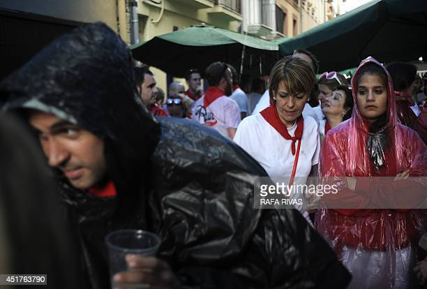 Revellers try to shelter from heavy rainfall on the first day of the San Fermin Festival in Pamplona northern Spain on July 6 2014 A redandwhite sea...