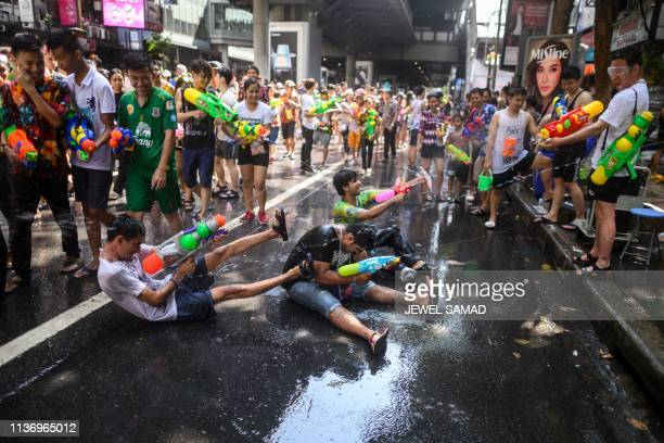 Revellers use water guns to spray at one another as they celebrate the Buddhist New Year, locally known as Songkran, in Bangkok on April 14, 2019.