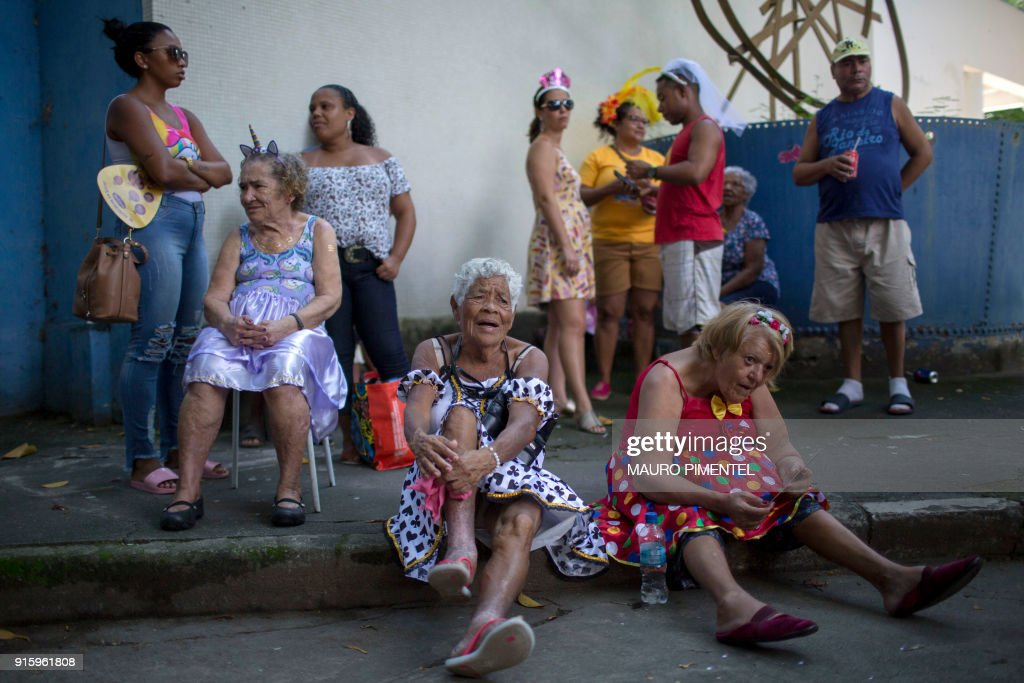 Revellers wait for the start of the street carnival parade of the 'Loucura Suburbana' bloco at the Engenho de Dentro neighborhood in Rio de Janeiro, Brazil, on February 8, 2018. The 'Loucura Suburbana' street carnival group is organized by workers and patients at the Nise da Silveira psychiatric hospital. The parade starts inside the hospital and winds its way through the streets of the neighborhood. /