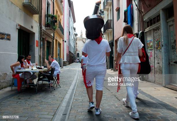 Revellers walk on the street on the first day of the San Fermin bull run festival in Pamplona northern Spain on July 7 2018 Each day at 8am hundreds...